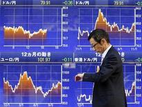 El Índice Nikkei subió al máximo de dos meses el miércoles por ganancias de las exportadoras después de que el yen cayera a un mínimo de siete meses contra el dólar por expectativas de que un nuevo gobierno en Japón presionará al banco central para que introduzca más estímulos monetarios. En la imagen ,un hombre pasa frente a un tablero electrónico con los tipos de cambio, en Tokio, el 8 de noviembre de 2012. REUTERS/Yuriko Nakao