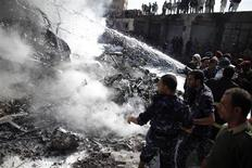 Firefighters extinguish fire from the wreckage of a plane after it crashed in Sanaa November 21, 2012. REUTERS/ Khaled Abdullah