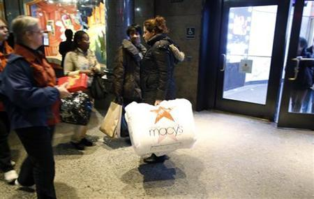 A woman walks out of Macy's department store with shopping bags as the busy holiday shopping season begins in New York, November 17, 2012. REUTERS/Carlo Allegri