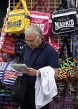 La llegada de turistas internacionales a España bajó en octubre un 3,2 por ciento hasta un total de 5,1 millones, según datos facilitados el jueves por Frontur, perteneciente al Ministerio de Industria, Energía y Turismo. En la imagen, un turista comprueba un mapa frente a una tienda de souvenirs en el centro de Madrid, el 2 de octubre de 2012. REUTERS/Sergio Perez