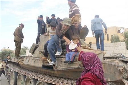 Residents are seen on a tank after Free Syrian Army fighters said they had defeated government troops at a military base at the town of Atareb near Aleppo November 19, 2012. REUTERS/Omar Ezzdin/Shaam News Network/Handout