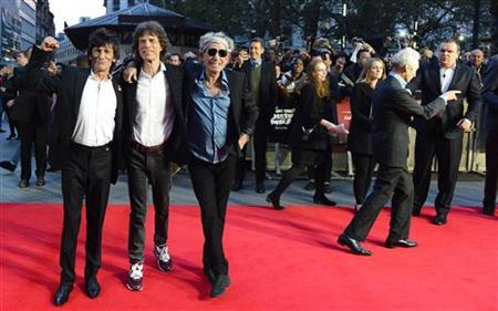 The Rolling Stones Ronnie Wood (L), Mick Jagger (2nd L) and Keith Richards (3rd L) pose for a photograph, as Charlie Watts (R) walks away, at the world premiere of ''Crossfire Hurricane'' at the Odeon Leicester Square in London October 18, 2012. REUTERS/Paul Hackett/Files