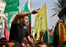La tregua entre Israel y el movimiento islamista Hamás se mantenía el jueves y los gazatíes lo celebraban como una victoria palestina, pese a que ambos bandos dicen estar preparados para apretar el gatillo en cualquier momento. En la imagen, un palestino celebra lo que los palestinso consideran una victoria sobre Israel tras ocho días de conflicto, durante una manifestación en Ciudad de Gaza, el 22 de noviembre de 2012. REUTERS/Suhaib Salem