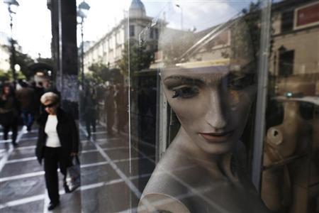 A woman walks past mannequins in a closed shop at central Athens November 15, 2012. REUTERS/John Kolesidis
