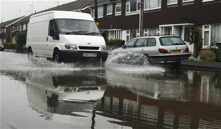 A van drives through flood water at Littlehampton in southern England June 11, 2012. REUTERS/Luke MacGregor