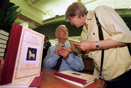 Author Bryce Courtenay (L) holds the hand of a lady after he signed a copy of his latest book titled ''The Night Country'' for her at a Sydney bookstore in this April 3, 1998 file photo. Best-selling Australian author Courtenay, who wrote about the struggles of life in Australia and South Africa, died at his home in Canberra, his publisher said on November 23, 2012, just two weeks after his latest novel was published. His death late on Thursday came less than three months after he told fans he had stomach cancer. He was 79. REUTERS/David Gray/Files