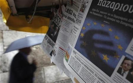 A man passes by a newspaper featuring the Euro currency sign in central Athens November 21, 2012. International lenders failed for the second week to reach a deal to release emergency aid for Greece and will try again next Monday, but Germany signalled that major divisions remain. REUTERS/John Kolesidis (GREECE - Tags: POLITICS BUSINESS)
