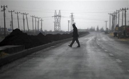 A Turkish man walks at a road during heavy rain on the Turkish border town of Ceylanpinar, Sanliurfa province November 23, 2012. Syria has denounced Turkey's request that NATO deploy Patriot defence missiles near its border with Syria, making its first response to the move by Ankara earlier this week.REUTERS/Amr Abdallah Dalsh (TURKEY - Tags: CIVIL UNREST MILITARY POLITICS CONFLICT)