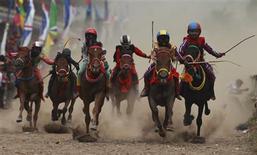 Child jockeys race their horses at a racetrack outside Bima, November 17, 2012. REUTERS/Beawiharta