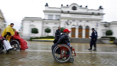A disabled man pushes himself on his wheelchair in front of the Bulgarian Parliament building in Sofia October 21, 2010. REUTERS/Stoyan Nenov/Files