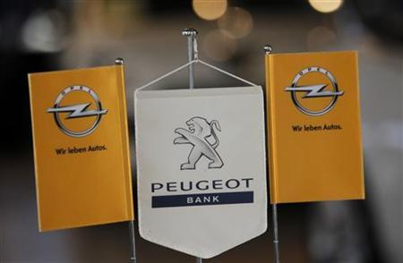 The logo of German General Motors daughter Opel and the bank of French car maker Peugeot are seen at a Opel and Peugeot dealership in Leverkusen near Cologne October 22, 2012. Picture taken October 22. REUTERS/Wolfgang Rattay (GERMANY)