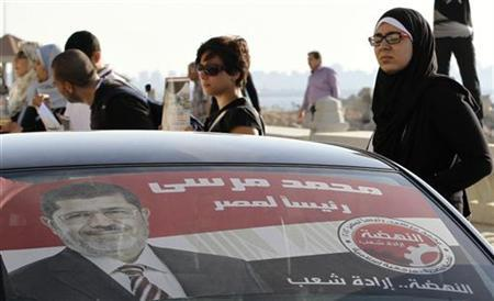 A car passes by with a poster of presidential candidate Mohamed Mursi, the head of the Muslim Brotherhood's political party as people stand in silence for the second anniversary of the death of Egyptian Khaled Said, in the port city of Alexandria June 6, 2012. REUTERS/Mohamed Abd El Ghany