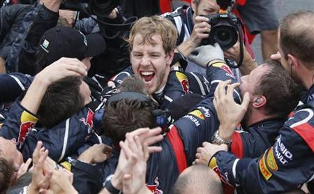 Red Bull Formula One driver Sebastian Vettel of Germany celebrates winning the world championship with his team after finishing sixth in the Brazilian F1 Grand Prix at Interlagos circuit in Sao Paulo November 25, 2012. REUTERS/Sergio Moraes