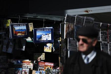 A man walks past a kiosk selling newspapers and magazines in Athens November 26, 2012. Euro zone finance ministers and the International Monetary Fund will seek to unfreeze the second bailout package for Greece on Monday, but they first need to agree if some of the official loans to Athens might eventually be forgiven to cut Greek debt. REUTERS/Yorgos Karahalis (GREECE - Tags: POLITICS BUSINESS MEDIA)
