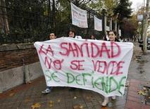 """Los trabajadores de la sanidad pública madrileña comenzaron el domingo por la noche una huelga de 48 horas para exigir la retirada del plan de sostenibilidad que pretende imponer el Gobierno autonómico, que según los convocantes supone una """"privatización encubierta"""" de la sanidad, además de la pérdida de más de 1.000 puestos de trabajo. En la imagen, trabajadores sanitarios con una pancarta en los exteriores del hospital del Niño Jesús, en Madrid, el 26 de noviembre de 2012. REUTERS/Andrea Comas"""