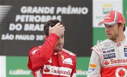 Aunque el piloto de Ferrari Fernando Alonso califica 2012 como su mejor temporada en la Fórmula Uno, el asturiano dice que el coche debe ser más rápido el año que viene si quiere volver a luchar por el título. En la imagen, el piloto de Ferrari Fernando Alonso (izquierda) gesticula en el podio ante el británico de McLaren Jenson Button, tras el Gran Premio de Interlagos en Sao Paulo, el 25 de noviembre de 2012. REUTERS/Paulo Whitaker