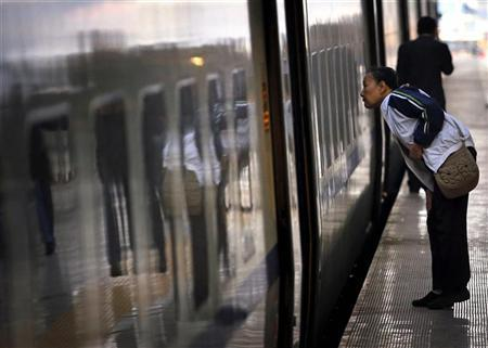 A woman peers into the carriage of a train as it prepares to leave the central railway station of the Chinese city of Zhengzhou, Henan Province October 30, 2012. REUTERS/David Gray