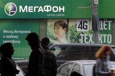 Люди проходят мимо салона связи Мегафона в Москве 26 ноября 2012 года. Книга заявок на IPO Мегафона были подписана в понедельник, в том числе благодаря поддержке крупной заявки от глобального инвестфонда, говорят источники. REUTERS/Maxim Shemetov