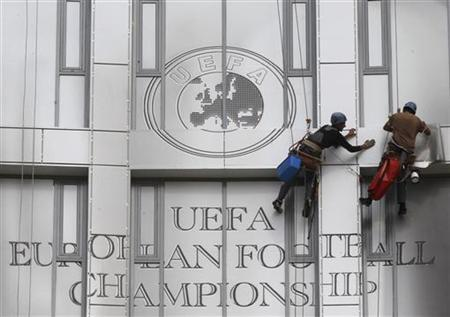 Workers abseil as they attach a huge placard displaying the Euro 2012 trophy as they decorate a building near the Olympic stadium in central Kiev June 6, 2012. REUTERS/Alexander Demianchuk/Files