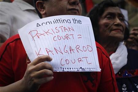 An activist holds a handwritten sign during a protest against a court decision in Karachi April 23, 2011. REUTERS/Athar Hussain/Files