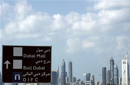 A sign which shows the way to the Dubai International Financial Center is seen with skyscrapers in the background in Dubai December 1, 2009. REUTERS/Ahmed Jadallah