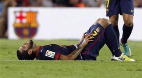 Dani Alves, do Barcelona, geme após ser lesionado durante partida contra o Real Madrid no estádio de Camp Nou em Barcelona, na Espanha. O lateral-direito ficará fora dos gramados por entre 15 e 20 dias devido a uma lesão na coxa. 7/10/2012 REUTERS/Albert Gea
