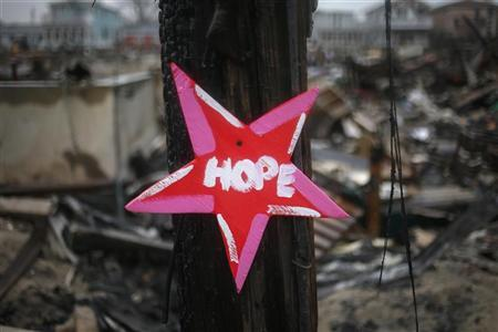 A wooden star with the word ''Hope'', is left in front of a burnt house in Breezy Point, almost a month after the neighborhood was left devastated by Hurricane Sandy, in the New York borough of Queens November 27, 2012. REUTERS/Adrees Latif