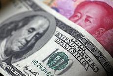 """Банкнота в $100 лежит на купюре в 100 юаней в Пекине, 9 мая 2011 года. Валюта Китая остается """"значительно недооцененной"""", заявила во вторник администрация президента Барака Обамы, воздержавшись, однако, от того, чтобы назвать вторую мировую экономику валютным манипулятором. REUTERS/Petar Kujundzic/Files"""