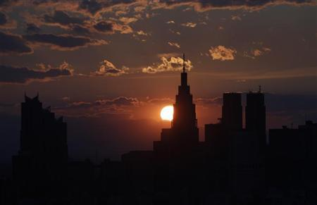 The sun goes down between skyscrapers in Tokyo May 11, 2012. REUTERS/Issei Kato