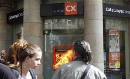 Homem olha caixa eletrônico do banco Catalunya Caixa pegando fogo durante protesto, em Barcelona. Autoridades de defesa da concorrência da União Europeia aprovaram nesta quarta-feira planos de reestruturação dos bancos espanhóis nacionalizados Bankia, NCG Banco, Catalunya Banc e Banco de Valencia. 11/10/2012 REUTERS/Albert Gea