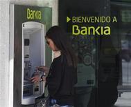 Женщина пользуется банкоматом Bankia в Мадриде 28 мая 2012 года. Органы регулирования конкуренции Евросоюза в среду одобрили план реструктуризации национализированных испанских банков Bankia, NCG Banco, Catalunya Banc и Banco de Valencia. REUTERS/Sergio Perez