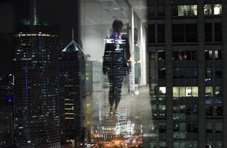 A woman is reflected in a window of an office in the financial district of Pudong in Shanghai September 22, 2011. REUTERS/Carlos Barria/Files