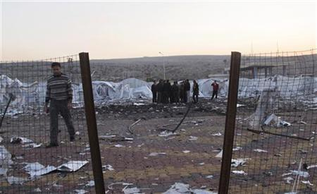Free Syrian Army (FSA) fighters inspect the damage at an unfinished refugee camp that the FSA says was destroyed by Syrian regime air strikes in Bab Al-Hawa, near the Syria-Turkey border, November 26, 2012. Picture taken November 26, 2012. REUTERS/Abdalghne Karoof (SYRIA - Tags: CONFLICT)