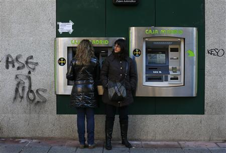 Women use an ATM machine at a branch of Spain's nationalized lender Caja Madrid-Bankia next to the word ''Assassins'' (L) in Madrid November 28, 2012. REUTERS/Susana Vera