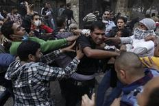 Protesters hit a riot policeman (C) after surrounding him during clashes in front of the U.S Embassy near Tahrir Square in Cairo November 28, 2012. Hundreds of demonstrators were in Cairo's Tahrir Square for a sixth day on Wednesday to demand that President Mohamed Mursi rescind a decree they say gives him dictatorial powers, and two of Egypt's top courts stopped work in protest. REUTERS/Amr Abdallah Dalsh
