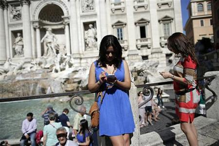 Women use smartphones in front of the Trevi Fountain in Rome September 20, 2012. REUTERS/Tony Gentile/Files