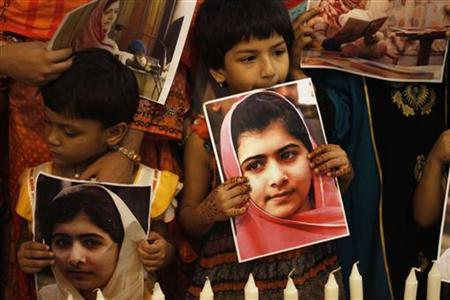 Children of supporters of the Muttahida Qaumi Movement (MQM) party hold potraits of Malala Yousufzai in Karachi November 10, 2012. REUTERS/Athar Hussain