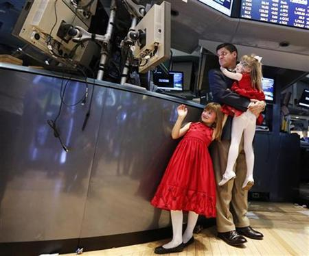 Trader Michael Guli monitors stocks with his daughters Taylor (standing) and Madison on the floor of the New York Stock Exchange, November 23, 2012. REUTERS/Brendan McDermid