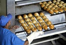 Padeiro tira fornada de pães do forno, em padaria de São Paulo, em novembro de 2002. Índice Geral de Preços-Mercado (IGP-M) registrou queda de 0,03 por cento em novembro, ante variação positiva de 0,02 por cento em outubro, influenciado principalmente pelo recuo dos preços no atacado e pela desaceleração dos alimentos no varejo, informou a Fundação Getulio Vargas. 06/11/2002 REUTERS/Paulo Whitaker