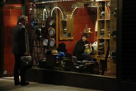 A shop worker looks out at a passer-by from a hat shop in London November 13, 2012. REUTERS/Luke MacGregor