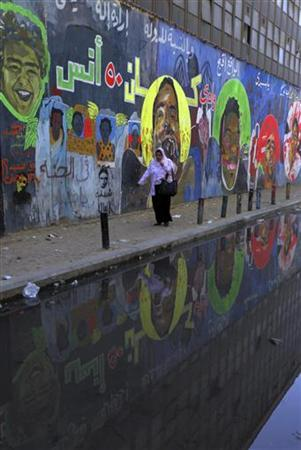A woman walks past a mural-covered wall at Mohamed Mahmoud street in Cairo November 29, 2012. An Islamist-led assembly was expected to finalise a new constitution on Friday aimed at transforming Egypt and paving the way for an end to a crisis which erupted when President Mohamed Mursi gave himself sweeping new powers last week. The street is the location where at least 42 protesters died during clashes in 2011 during Egypt's interim military rule. REUTERS/Amr Abdallah Dalsh (EGYPT - Tags: POLITICS)