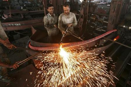 Labourers work inside an iron factory on the outskirts of Jammu November 12, 2012. India's economic gloom deepened on Monday with a surprise contraction in industrial production, a fall in exports and higher retail inflation, dashing hopes of a quick revival in an economy on track to post its slowest growth in a decade. REUTERS/Mukesh Gupta (INDIAN-ADMINISTERED KASHMIR - Tags: BUSINESS COMMODITIES)