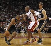 <p>Gary Neal (à gauche) des San Antonio Spurs tente de passer Ray Allen (au centre) du Miami Heat. Le patron de la NBA, David Stern, a promis des sanctions contre les Spurs, coupables à ses yeux d'avoir gâché l'affiche de la soirée jeudi en laissant leurs meilleurs joueurs au repos pour le match sur le parquet de la franchise floridienne, qui s'est soldé par une victoire 105 à 100 du Heat. /Photo prise le 29 novembre 2012/REUTERS/Robert Sullivan</p>