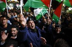 """Палестинцы празднуют в Рамалле повышение статуса Палестины в ООН 29 ноября 2012 года. Генеральная ассамблея ООН в четверг подавляющим большинством голосов одобрила фактическое признание суверенного государства Палестины, после того как палестинский президент Махмуд Аббас призвал выдать долгожданное """"свидетельство о рождении"""". REUTERS/Marko Djurica"""