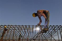 A worker welds iron rods at the construction site of a commercial complex in the western Indian city of Ahmedabad November 29, 2012. India's economy extended its long slump in the last quarter, with lower-than-expected growth keeping it on track for its worst year in a decade and underscoring the urgency of politically difficult reforms to spur a revival. Picture taken November 29, 2012. REUTERS/Amit Dave