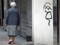 El Gobierno español ha decidido no actualizar de forma generalizada las pensiones de acuerdo con la inflación registrada en 2012, y adicionalmente ha anunciado que cambia la ley vigente para poder acudir al fondo de reserva de la Seguridad Social para hacer frente al pago extra de Navidad de las pensiones. En la imagen de archivo, una señora mayor pasea a su perro en Pontevedra, el 18 de septiembre de 2012. REUTERS/Miguel Vidal