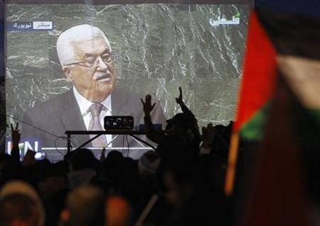 Palestinians take part in a rally while the speech of Palestinian President Mahmoud Abbas is projected in the West Bank city of Ramallah November 29, 2012. REUTERS/Marko Djurica