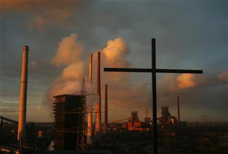 A cross atop a hill is pictured in front of a coking plant at the steelworks of German steel maker ThyssenKrupp AG in Bruckhausen, a suburb of the western German city of Duisburg October 2, 2012. Picture taken October 2. REUTERS/Ina Fassbender