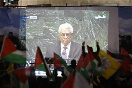 Palestinians take part in a rally while the speech of Palestinian President Mahmoud Abbas is being projected in the West Bank city of Ramallah November 29, 2012. REUTERS/Mohamad Torokman