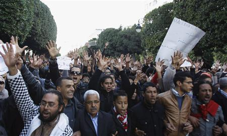 Demonstrators hold up signs and shout slogans outside the interior minister's office in Tunis, during a protest against police violence in Siliana November 30, 2012. At least 200 people were injured when demonstrators demanding jobs clashed with police on Tuesday and Wednesday in Siliana, a city on the edge of the Sahara whose inhabitants have long complained of neglect. REUTERS/Zoubeir Souissi